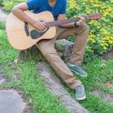 muchacho que toca la guitarra en el parque de naturaleza al aire libre Imagen de archivo
