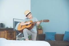 Muchacho que toca la guitarra en sala de estar en casa Foto de archivo libre de regalías