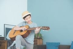 Muchacho que toca la guitarra en sala de estar en casa Foto de archivo