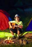 Muchacho que toca una guitarra, campamento de verano Imagen de archivo