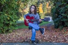 Muchacho que toca una guitarra roja Imagenes de archivo
