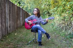 Muchacho que toca una guitarra roja Imágenes de archivo libres de regalías