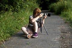 Muchacho que toma imágenes con el trípode  Imagen de archivo
