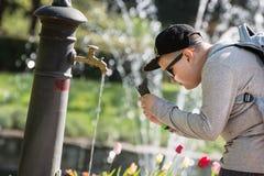 Muchacho que toma la foto - agua potable que fluye del grifo Imagen de archivo libre de regalías