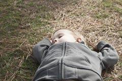 Muchacho que toma a Nap On Grass Imagenes de archivo