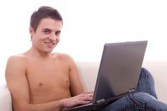 Muchacho que trabaja con la computadora portátil en el sofá Fotos de archivo libres de regalías