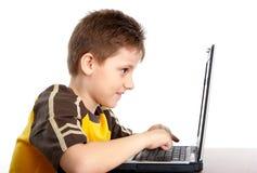 Muchacho que trabaja con la computadora portátil Imagen de archivo