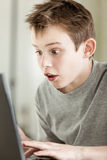 Muchacho que trabaja en el ordenador portátil con la cara sorprendente Fotografía de archivo