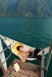 Muchacho que trabaja en hamaca en el lago Imagen de archivo