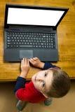 Muchacho que trabaja en un ordenador portátil Foto de archivo libre de regalías