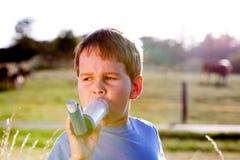 Muchacho que usa el inhalador para el asma en pasto Imagen de archivo