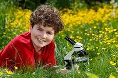 Muchacho que usa el microscopio al aire libre Imágenes de archivo libres de regalías