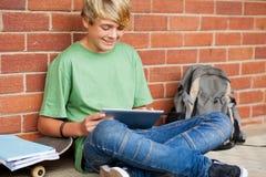 Muchacho que usa el ordenador de la tablilla Imagen de archivo