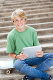Muchacho que usa el ordenador de la tablilla Foto de archivo