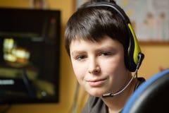 Muchacho que usa el ordenador en casa, jugando al juego Fotografía de archivo libre de regalías