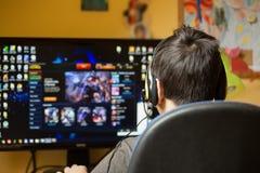Muchacho que usa el ordenador en casa, jugando al juego Imágenes de archivo libres de regalías