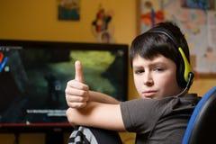 Muchacho que usa el ordenador en casa, jugando al juego Imagen de archivo libre de regalías