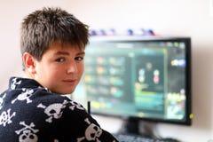 Muchacho que usa el ordenador en casa, jugando al juego Imagenes de archivo
