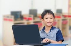 Muchacho que usa el ordenador portátil Fotos de archivo libres de regalías