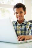 Muchacho que usa el ordenador portátil en casa Imágenes de archivo libres de regalías