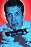 Muchacho que usa el regulador del juego video. JUGUEMOS Imagen de archivo