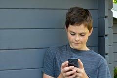 Muchacho que usa el teléfono móvil Fotografía de archivo