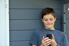 Muchacho que usa el teléfono móvil Fotos de archivo