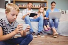 Muchacho que usa el teléfono móvil mientras que familia con tecnologías en fondo Fotografía de archivo