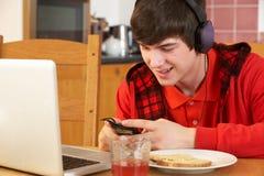 Muchacho que usa electrónica mientras que come el desayuno Foto de archivo libre de regalías