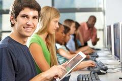 Muchacho que usa la tableta de Digitaces en clase del ordenador Imagen de archivo