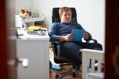 Muchacho que usa la tableta de Digitaces en dormitorio Imagen de archivo libre de regalías