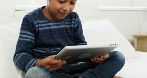 Muchacho que usa la tableta digital mientras que se relaja en cama