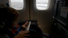 Muchacho que usa la tableta en el avión que va a sacar almacen de video