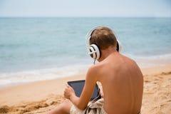 Muchacho que usa la tableta que se sienta por el mar Imágenes de archivo libres de regalías