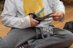 Muchacho que usa las tijeras del metal para cortar una cinta de un objeto decorativo de la Navidad Fotos de archivo libres de regalías
