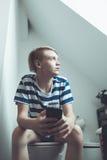 Muchacho que usa smartphone en cuarto de baño Imagen de archivo libre de regalías