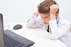 Muchacho que usa su ordenador portátil Fotos de archivo libres de regalías