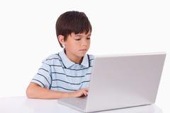 Muchacho que usa un ordenador portátil Imagen de archivo libre de regalías
