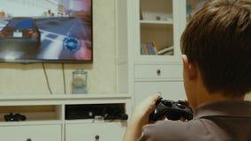 Muchacho que usa un regulador para jugar un videojuego imagenes de archivo