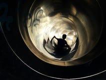 Muchacho que va abajo de una diapositiva hacia la luz Imagen de archivo