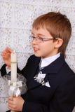 Muchacho que va a la primera comunión santa con la vela Imagen de archivo libre de regalías