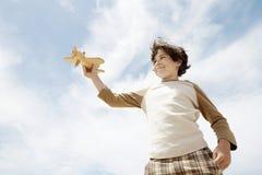 Muchacho que vuela a Toy Airplane Against Cloudy Sky Imagen de archivo