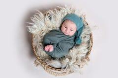 Muchacho recién nacido en el abrigo gris que miente en cesta Foto de archivo libre de regalías