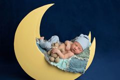 Muchacho recién nacido que duerme en la luna con Teddy Bear imagen de archivo
