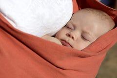 Muchacho recién nacido que duerme en portador de la honda del bebé fotografía de archivo libre de regalías