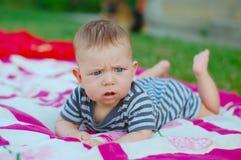 Muchacho recién nacido que miente en las mantas rosadas y blancas en hierba verde al aire libre Fotografía de archivo libre de regalías