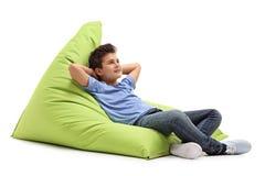 Muchacho relajado que pone en un beanbag foto de archivo