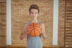 Muchacho resuelto que lleva a cabo un baloncesto Fotografía de archivo libre de regalías