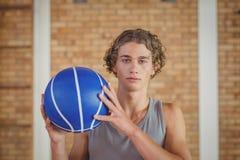 Muchacho resuelto que lleva a cabo un baloncesto Foto de archivo