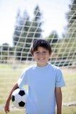 Muchacho retroiluminado con el balón de fútbol Imágenes de archivo libres de regalías